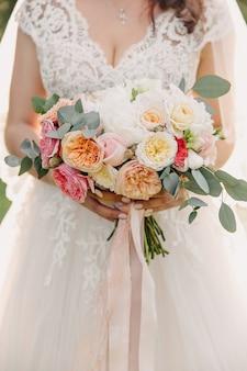 Noiva com um vestido de renda branca, segurando seu buquê de noiva feito de várias flores.