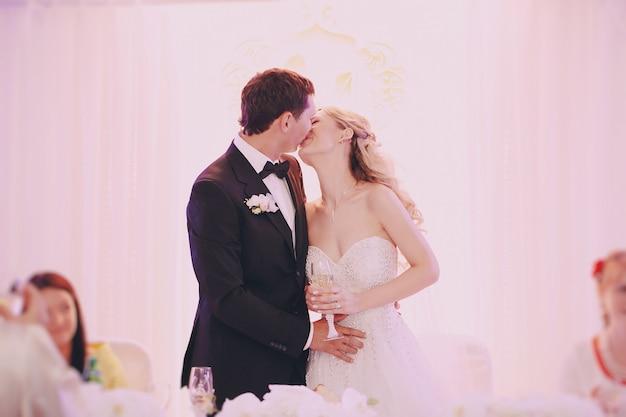 Noiva com uma taça de champanhe na mão beijando seu marido