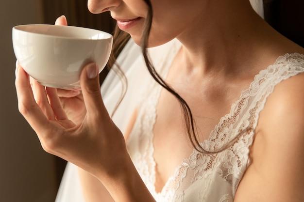 Noiva com uma xícara de café, manhã de casamento, preparação para o dia do casamento