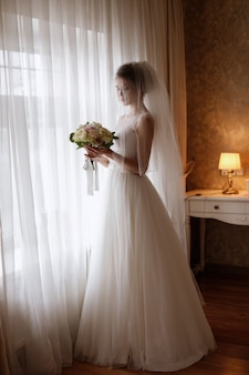Noiva com véu e com um buquê. o rosto dela está fechado. esperando o noivo