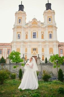 Noiva com véu na frente da igreja