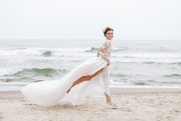 Noiva corre ao longo da praia do mar em um dia nublado