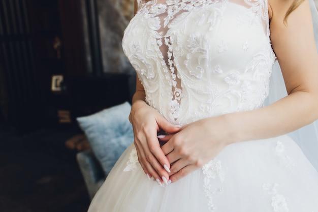 Noiva cruzou as mãos sobre os joelhos na expectativa do noivo. manhã da noiva.