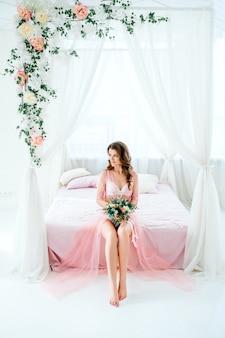 Noiva da manhã. a noiva em linho boudoir rosa lindo senta-se na cama e segura um buquê chique, um lindo penteado