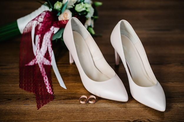 Noiva de acessório de casamento. elegantes sapatos bege laqueados, anéis de ouro, flores são isolados na mesa de pé sobre fundo de madeira.