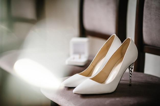 Noiva de acessório de casamento. elegantes sapatos brancos lacados, anéis de ouro são isolados em pé sobre fundo marrom.