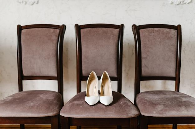 Noiva de acessório de casamento. elegantes sapatos brancos lacados, são isolados na cadeira em pé no fundo marrom.