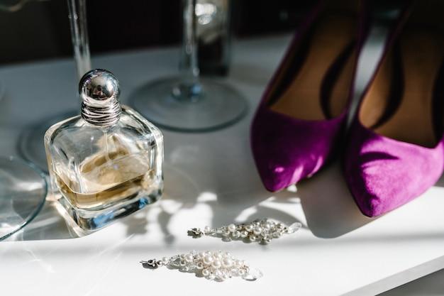 Noiva de acessório de casamento. sapatos violetas elegantes, brincos e perfumes na mesa de pé na mesa de fundo de madeira.
