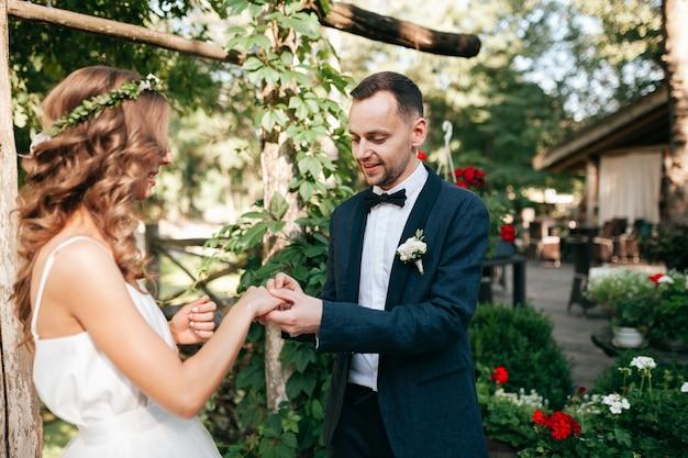 Noiva de beleza e noivo bonito estão usando anéis uns aos outros.