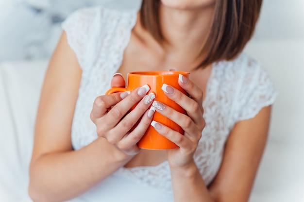 Noiva de beleza em vestido de noite está bebendo café