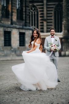 Noiva de belo retrato está dançando para o noivo e girando ao ar livre.