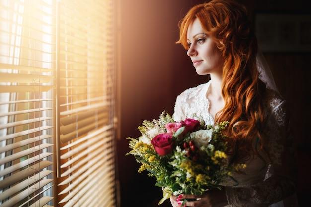 Noiva de cabelo vermelho lindo perto da janela