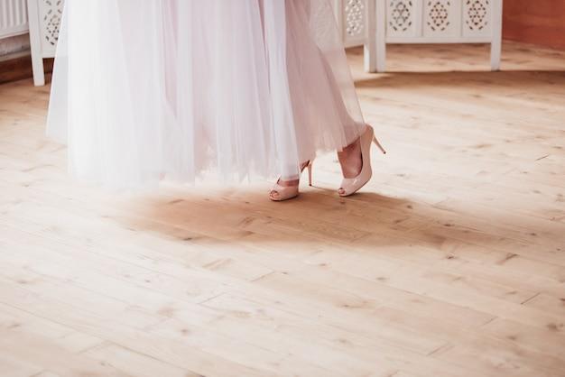 Noiva de manhã com dama de honra. prepare-se para o casamento. pernas da noiva. sapatos de casamento. vestidos de bainha.