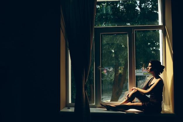 Noiva de manhã sentada no parapeito da janela