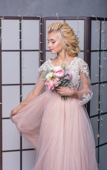 Noiva de moda beleza no estúdio interior com buquê de flores nas mãos. lindo retrato de noiva casamento maquiagem e penteado.