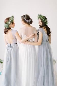 Noiva de pé com as costas em um vestido de noiva branco com duas damas de honra em vestidos azuis