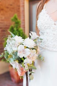Noiva de recém-casado, segurando o buquê de flores brancas