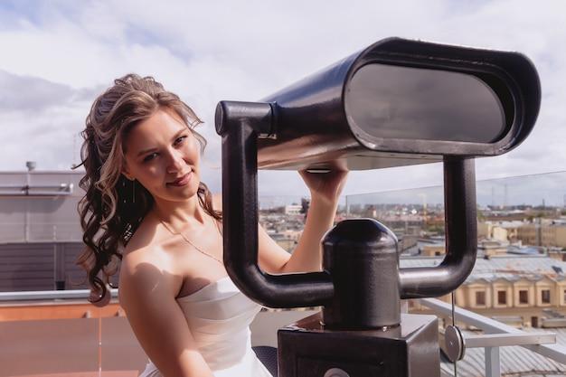 Noiva de retrato no deck de observação fica no telhado com vista panorâmica da cidade velha. mulher bonita em vestidos de noiva no dia ensolarado de casamento