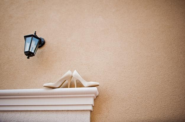Noiva de sapatos de casamento na frente da casa com uma lanterna