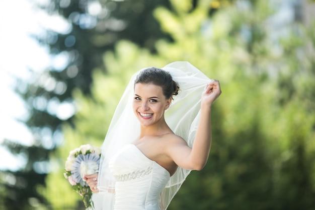Noiva de sorriso que prende um ramalhete
