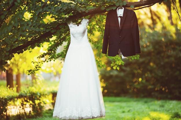 Noiva de traje de vestido de casamento para o noivo em uma árvore no parque