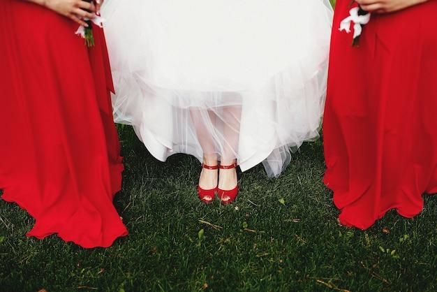 Noiva de vestido branco com damas de honra em vestidos vermelhos na grama verde.