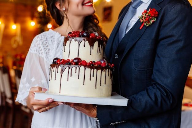 Noiva de vestido branco e noivo de terno azul, segurando nas mãos um bolo de casamento branco de dois níveis, decorado com frutas vermelhas e bagas, ensopados em chocolate