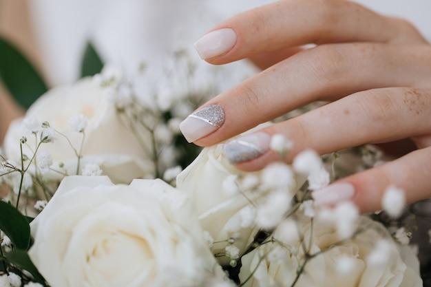 Noiva demonstra sua manicure sobre o buquê de casamento