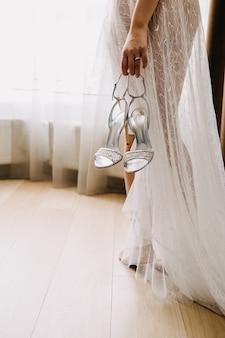 Noiva descalça segurando sapatos de casamento