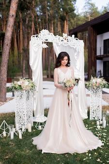 Noiva deslumbrante em um vestido bege está diante de um altar de casamento fora