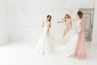 Noiva e dama de honra bonitas felizes que ajustam seu vestido de casamento. Beber champanhe.