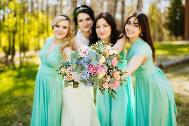 Noiva e damas de honra com buquês de casamento. momento alegre de recepção de casamento ensolarado.