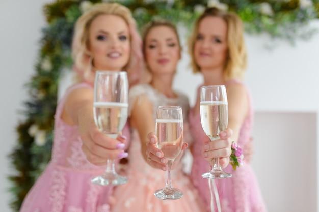 Noiva e damas de honra comemoram o dia do casamento e bebem champanhe rosa de copos juntos