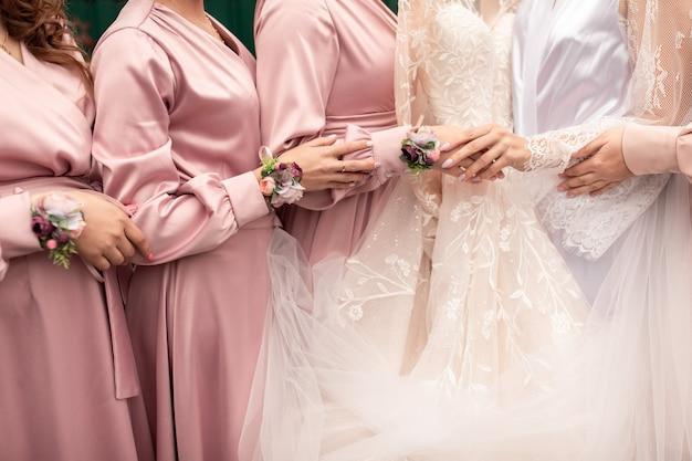 Noiva e damas de honra em vestidos cor de rosa, de mãos dadas no dia do casamento