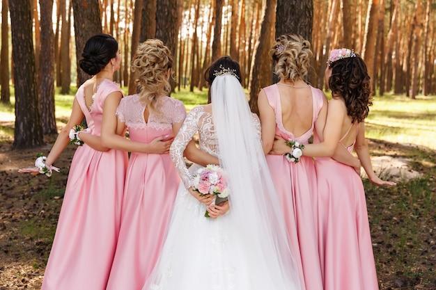 Noiva e damas de honra em vestidos cor de rosa na floresta
