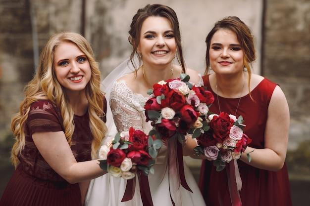 Noiva e damas de honra em vestidos vermelhos posam fora na velha rua molhada