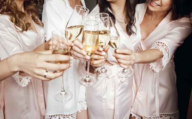 Noiva e damas de honra estão em vestes de seda com copos de champa
