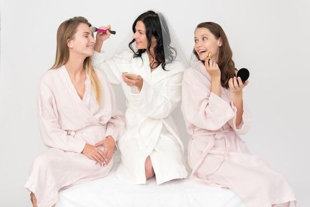 Noiva e damas de honra fazendo maquiagem para o outro