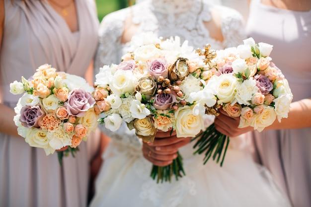 Noiva e damas de honra segurando buquês de casamento bonito.