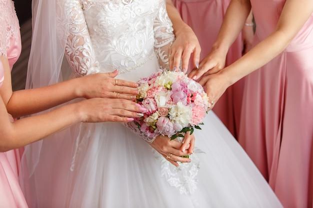 Noiva e damas de honra segurando o buquê de casamento