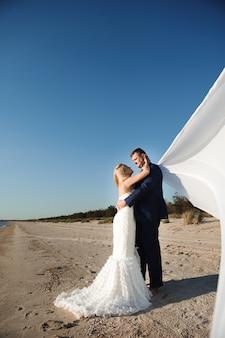 Noiva e noivo à beira-mar no dia do casamento