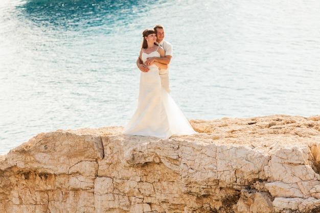 Noiva e noivo à beira-mar no dia do casamento.