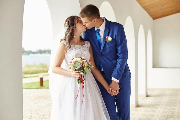 Noiva e noivo abraçam e beijam no casamento