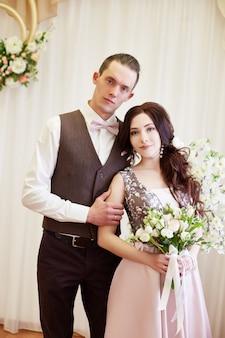 Noiva e noivo abraçam e posam para o casamento