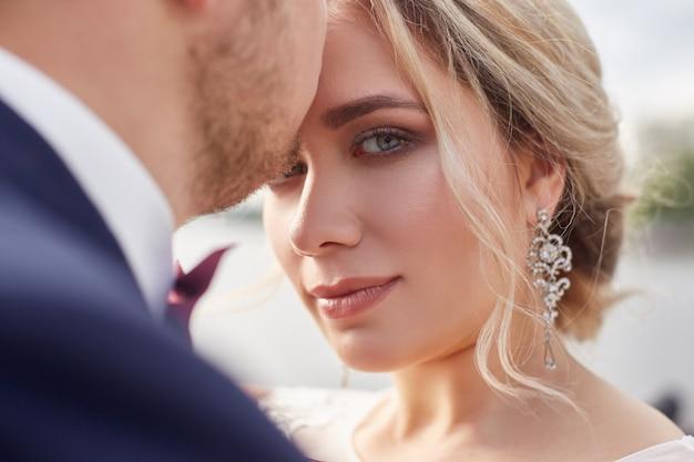 Noiva e noivo abraçando e beijando