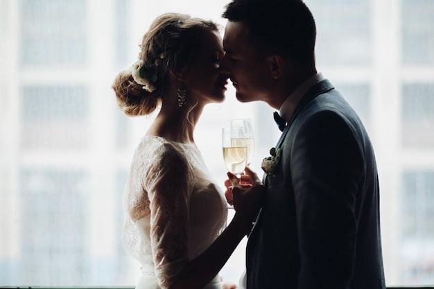 Noiva e noivo abraçando e segurando pelas mãos uns aos outros
