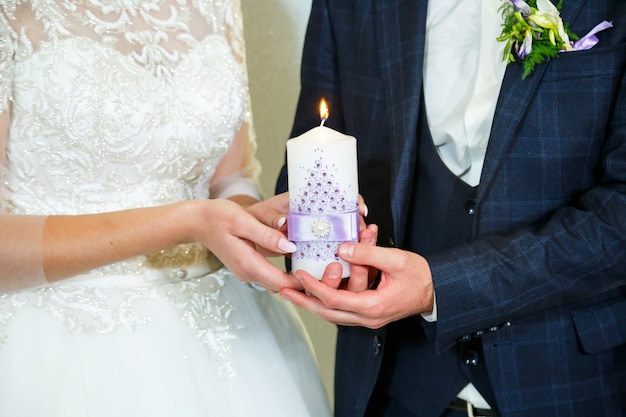 Noiva e noivo acendendo uma vela juntos no dia do casamento