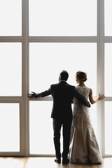 Noiva e noivo adultos se abraçam e ficam perto de uma grande janela, de costas para o espectador