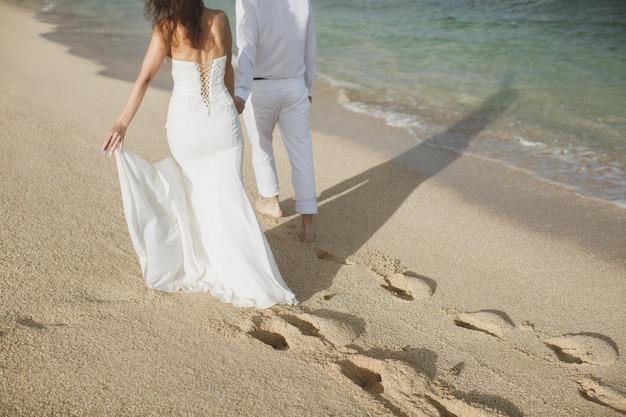 Noiva e noivo andando na areia