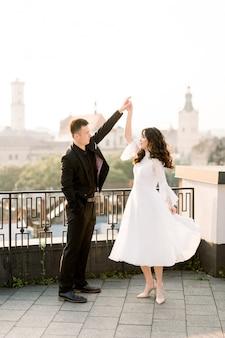 Noiva e noivo asiáticos bonitos novos no dia do casamento que andam e que dançam no telhado da cidade velha.